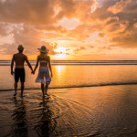 Couple walking on beach during sunset